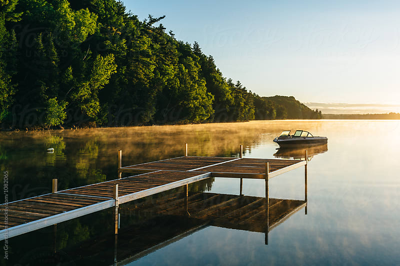 Boat and dock on a lake in the early morning by Jen Grantham for Stocksy United