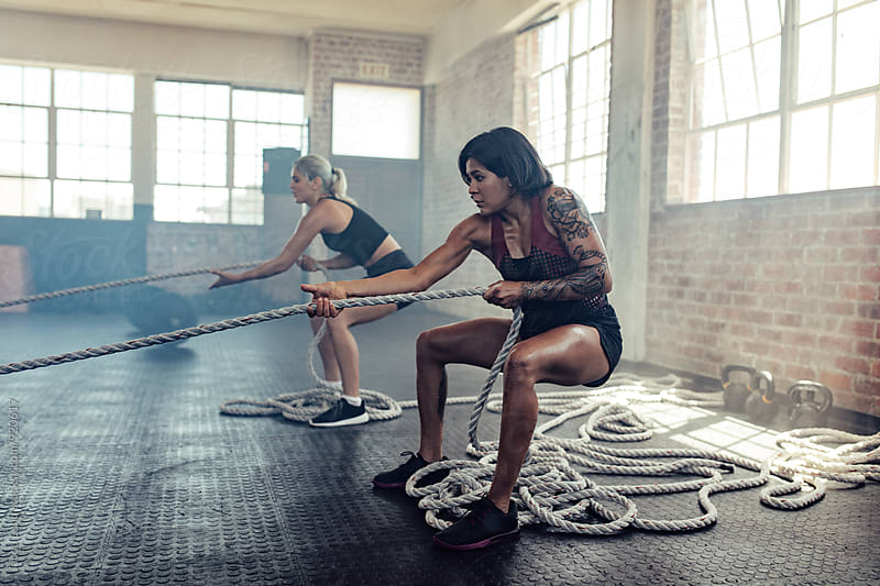 Strong women pulling ropes during workout by Jacob Ammentorp Lund for Stocksy United
