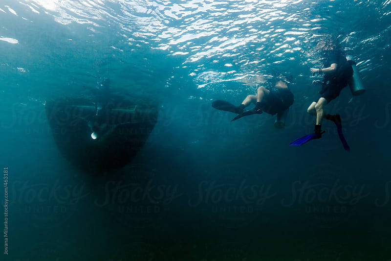 Scuba diver buddies in the sea at the surface next to a boat seen from underwater by Jovana Milanko for Stocksy United