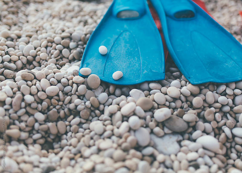 Blue flippers on stony beach by Dejan Ristovski for Stocksy United