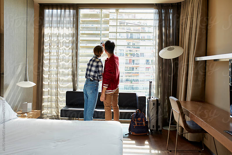 Couple Taking Selfie By Window In Hotel Room by ALTO IMAGES for Stocksy United