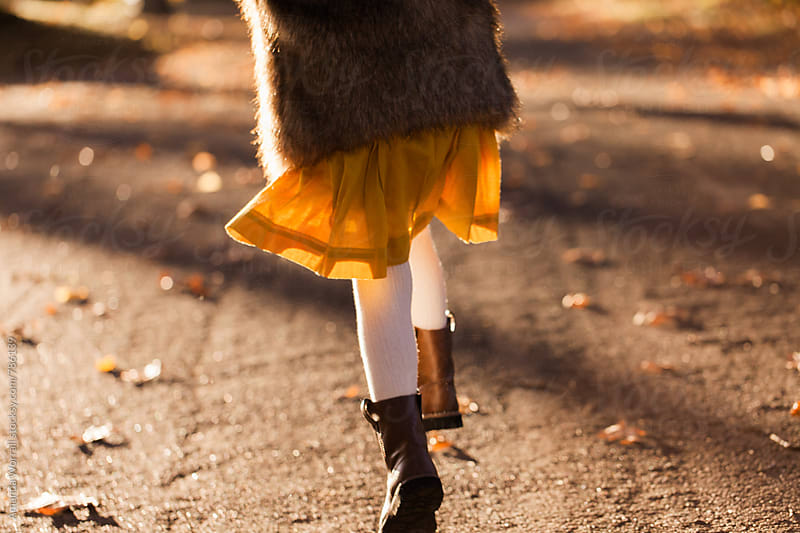 Close up of a girl's feet skipping down a path in autumn by Amanda Worrall for Stocksy United