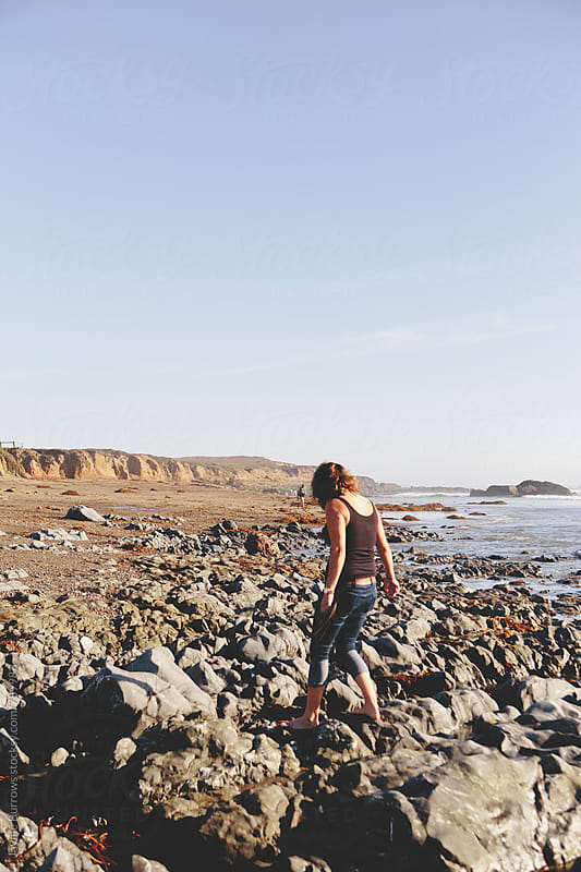 Woman Walks on Rocky Seaside Terrain by Jayme Burrows for Stocksy United