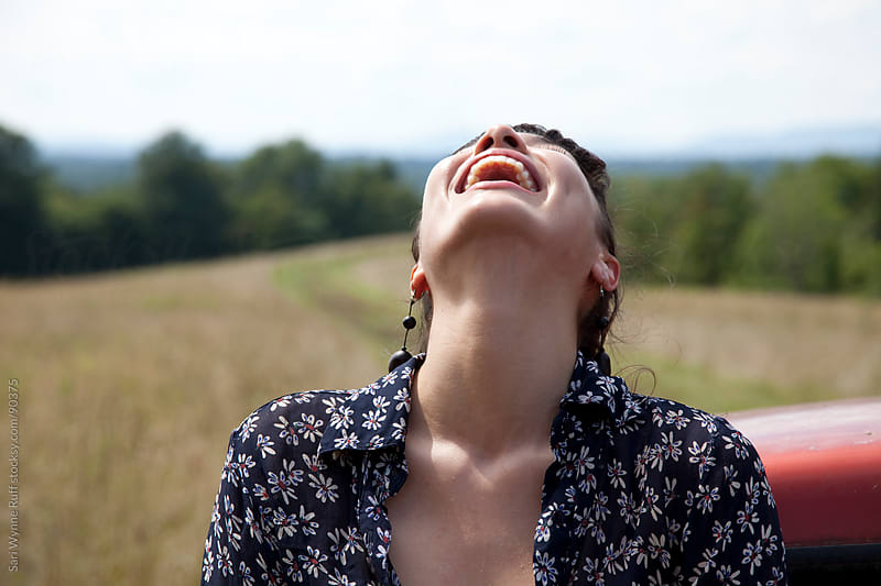 Woman Laughing in Field by Sari Wynne Ruff for Stocksy United