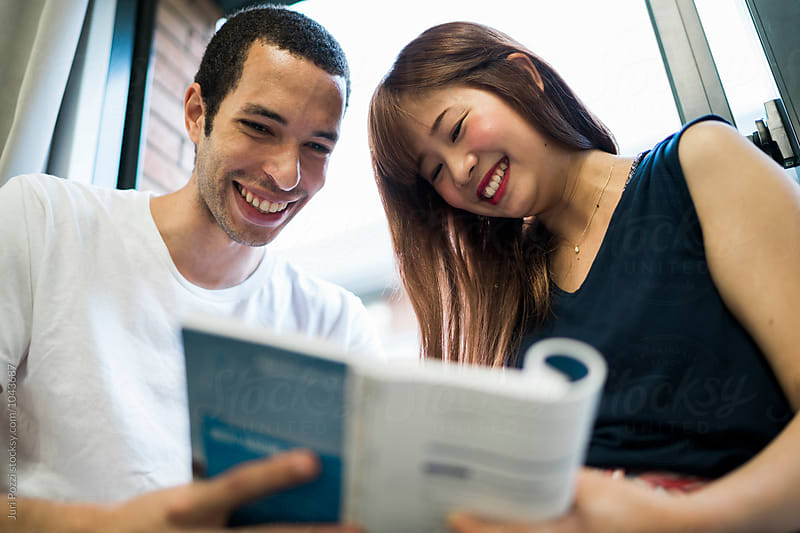 Mixed race students couple studying in a classroom in Japan by Juri Pozzi for Stocksy United