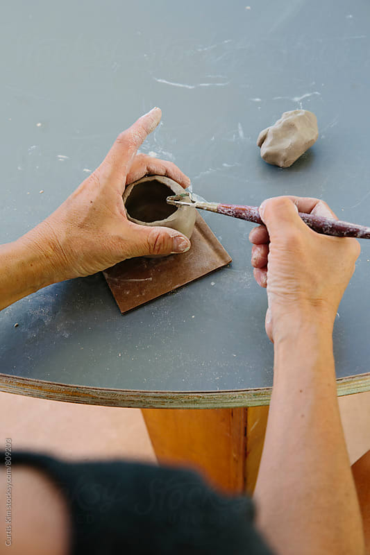 Ceramist working with clay in workshop by Curtis Kim for Stocksy United