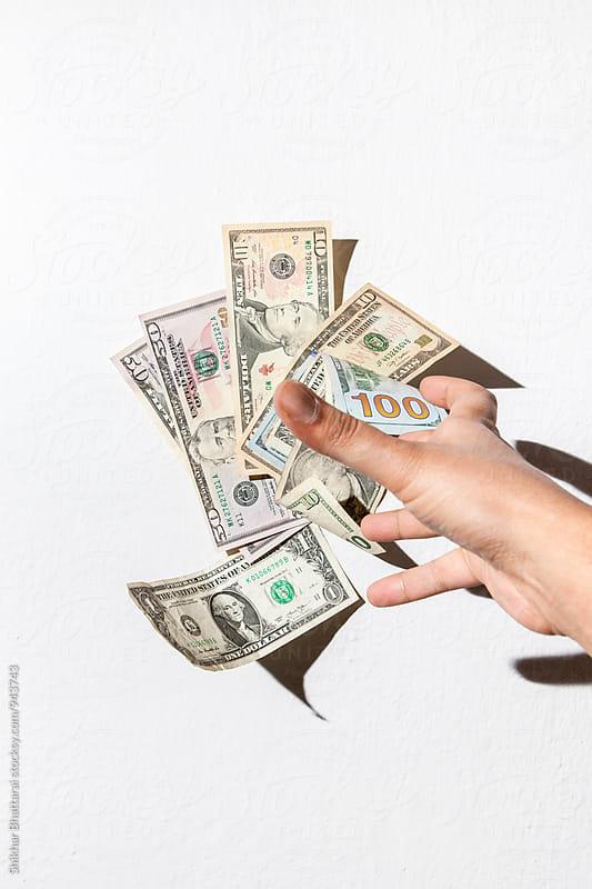 Stash of dollar bills thrown against a white wall. by Shikhar Bhattarai for Stocksy United