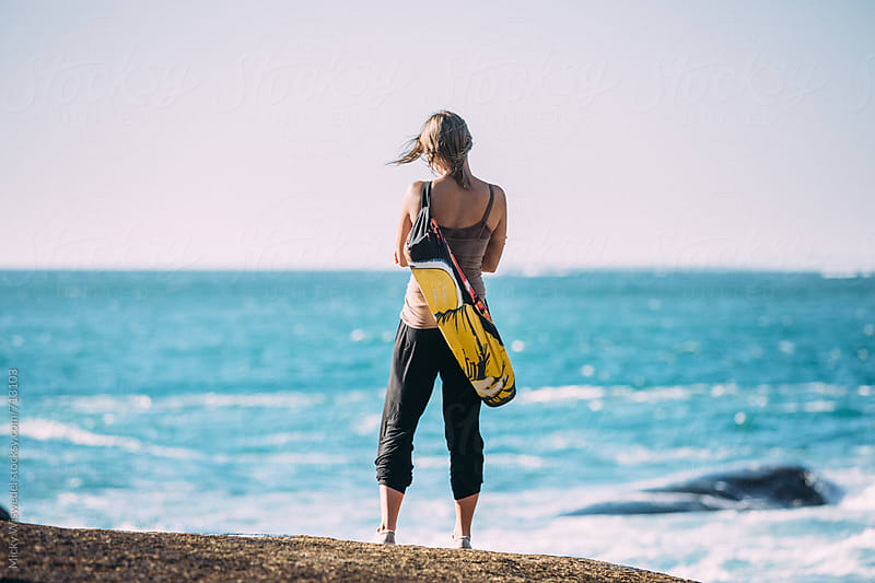 Woman with a yoga mat standing and enjoying the view of the sea by Micky Wiswedel for Stocksy United