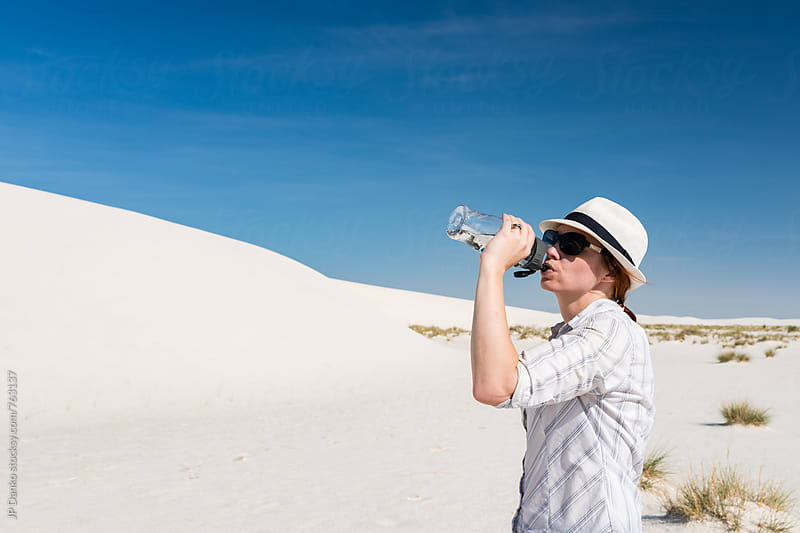 Woman Drinking from Water Bottle Sand Sledding In White Sands National Monument New Mexico by JP Danko for Stocksy United