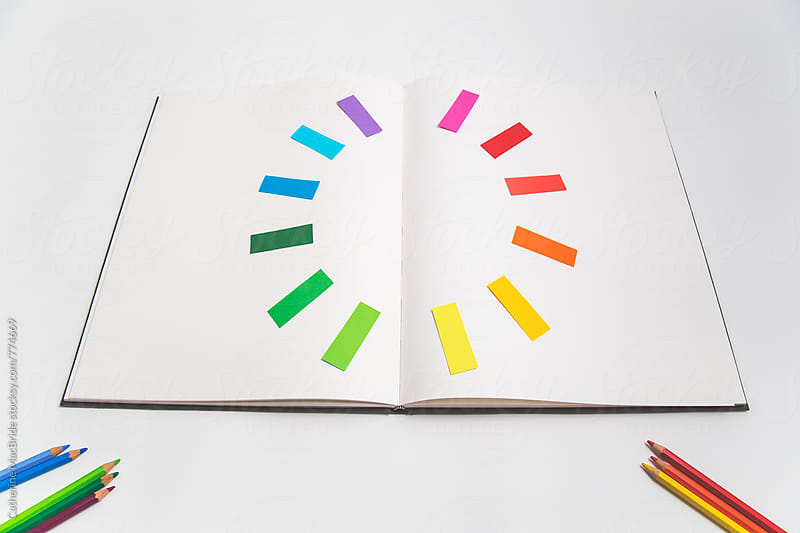 Colour wheel on open book with pencils... by Catherine MacBride for Stocksy United
