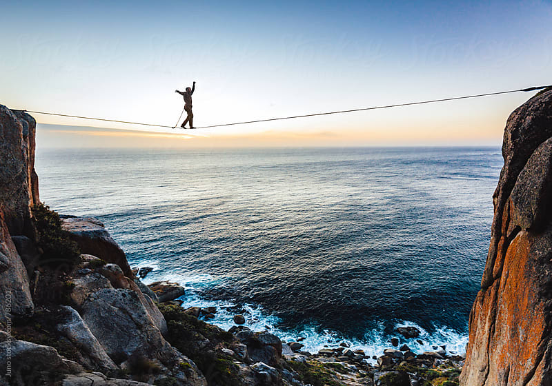 Man tightrope walking a highline between two cliffs overlooking the sea at sunset by Micky Wiswedel for Stocksy United