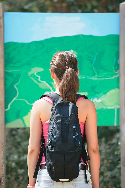 Back view of young hiker woman with backpack looking map on a forest road. by BONNINSTUDIO for Stocksy United