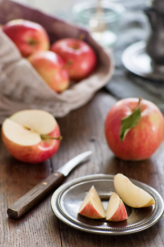 wedges of red apple in a plate by Laura Adani for Stocksy United