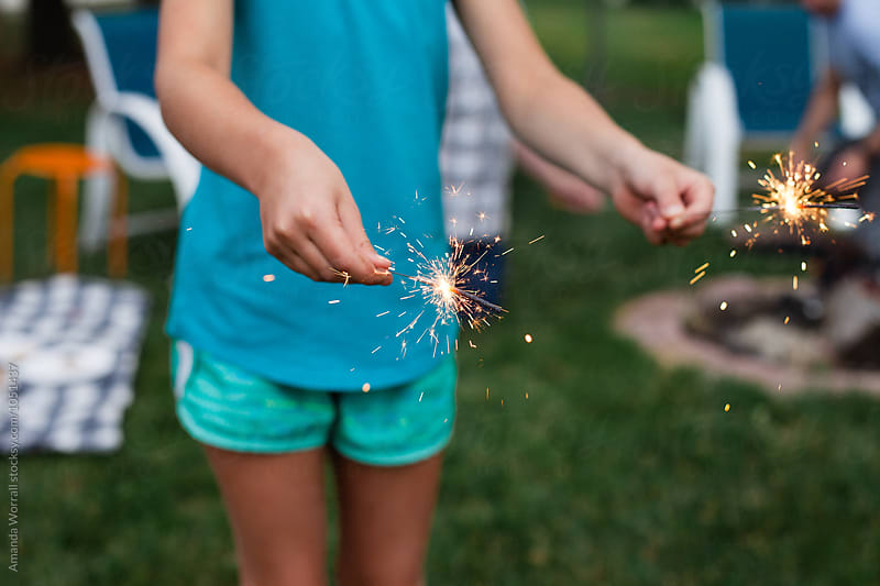 Anonymous child holding sparklers in each hand in the backyard by Amanda Worrall for Stocksy United