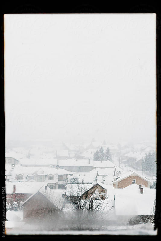 Snowy roofs looking through the window by Natasa Kukic for Stocksy United
