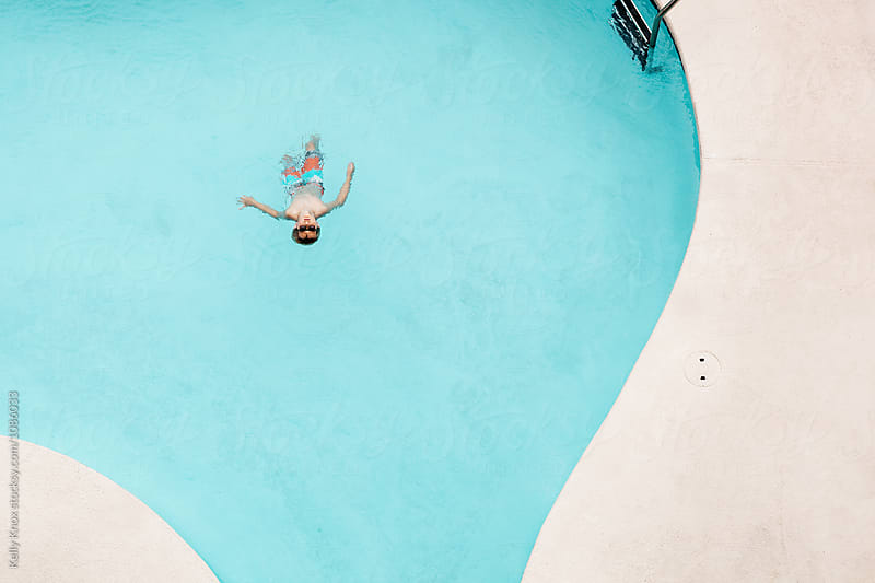 overhead image of a boy floating in a pool by Kelly Knox for Stocksy United
