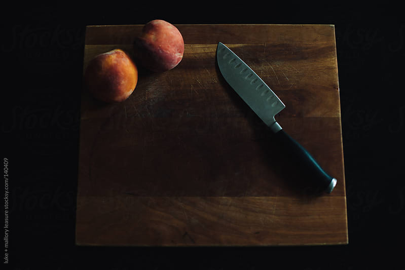 Peaches on a cutting board by luke + mallory leasure for Stocksy United