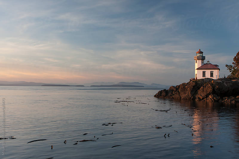 Lighthouse and calm water at sunset by Mihael Blikshteyn for Stocksy United