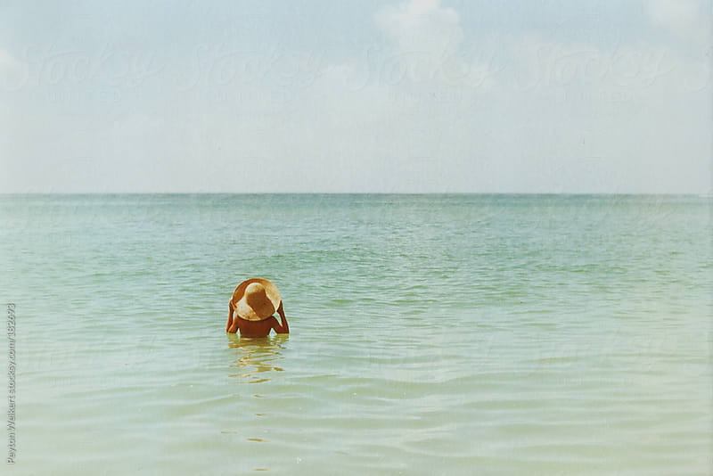 young girl walks through ocean while wearing a sun hat by Peyton Weikert for Stocksy United