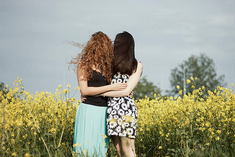 Two young woman hugging each other with hair covering their face by Jovana Rikalo for Stocksy United