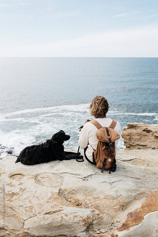 Man and his dog sitting on a cliff overlooking the ocean by KATIE + JOE for Stocksy United