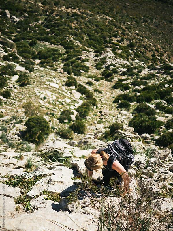 Girl climbing a rock in sunny el chorro by Martin Matej for Stocksy United