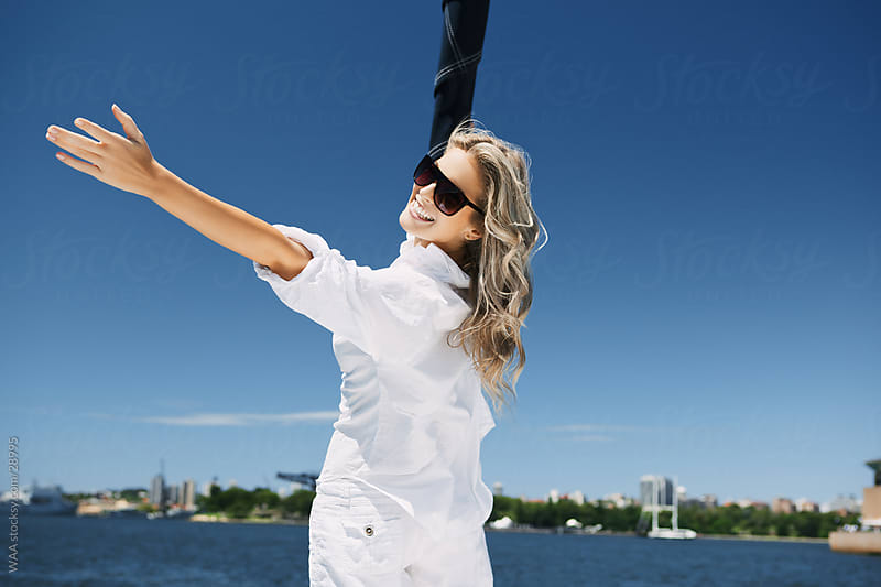 Happy young woman on sail boat by WAA for Stocksy United