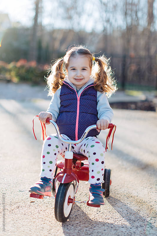 Adorable young girl with pigtails sitting on a tricycle by Jakob for Stocksy United