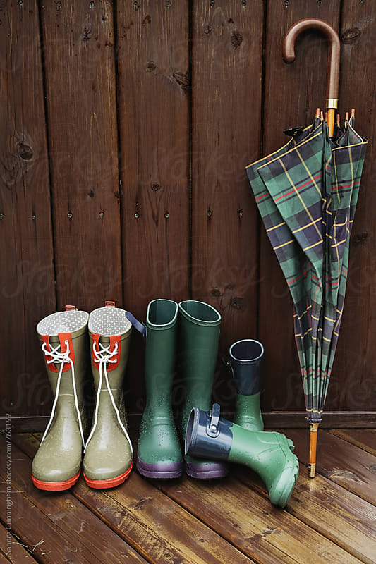 Rain boots with plaid umbrella on back porch by Sandra Cunningham for Stocksy United