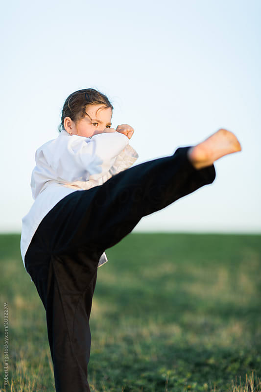 Girl doing martial arts outside on grass