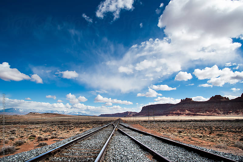 Railway to the canyon in a desert landscape by Jean-Claude Manfredi for Stocksy United
