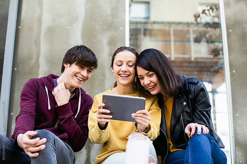 Group of teen friends watching a funny video on digital tablet. by BONNINSTUDIO for Stocksy United