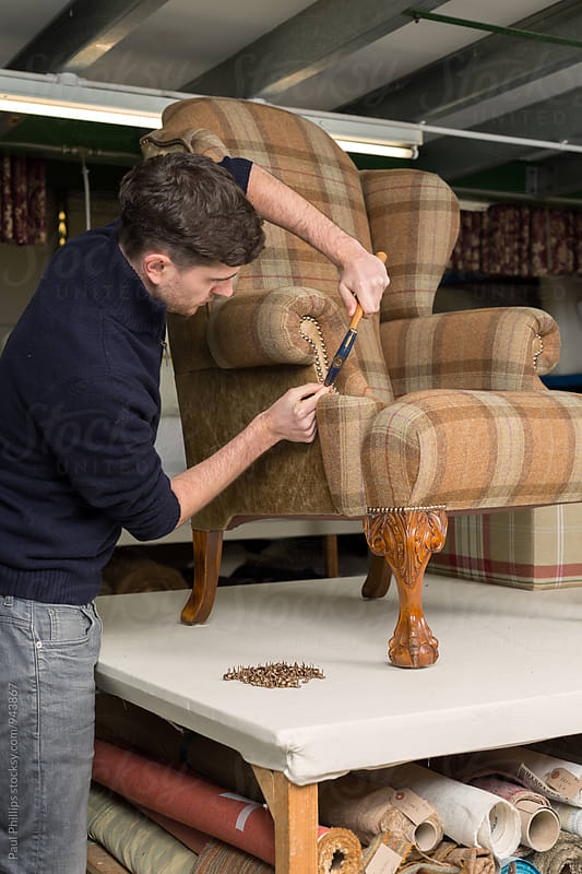 Craftsman attaching brass studs to the arm of a re-upholstered antique chair. by Paul Phillips for Stocksy United