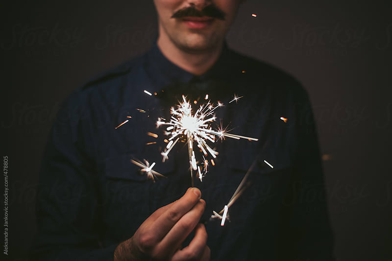 Man with mustache holding a sparkler by Aleksandra Jankovic for Stocksy United