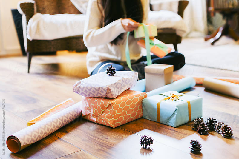 Anonymous woman wrapping Christmas gifts at home. by BONNINSTUDIO for Stocksy United
