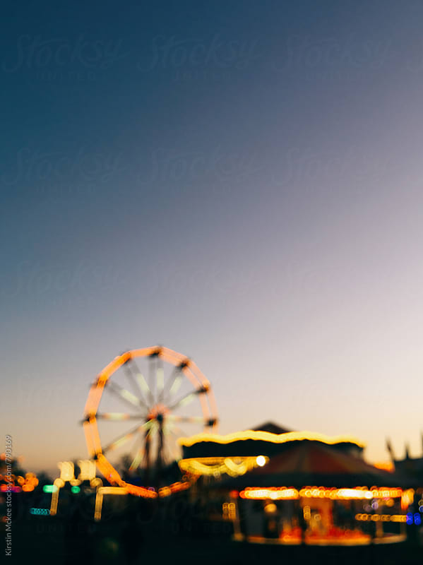 Out of focus image of funfair by Kirstin Mckee for Stocksy United