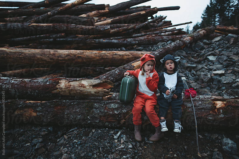 Kids dressed up like fox and raccoon sitting sadly on pile of clearcut logs by Rob and Julia Campbell for Stocksy United