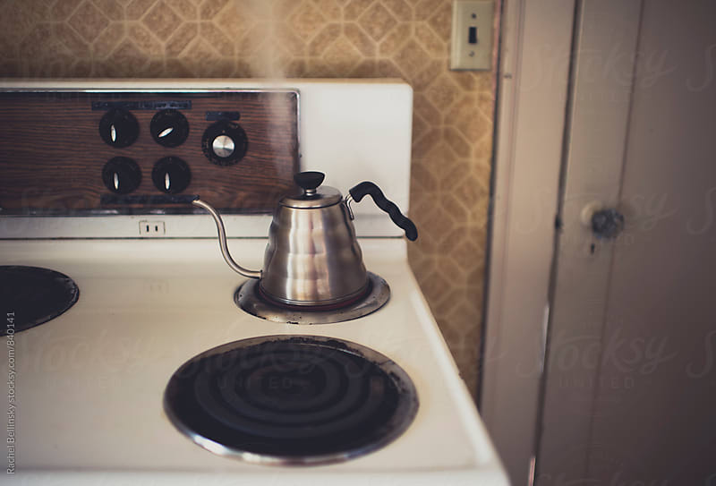 A vintage stove by an orange wall with a modern coffeepot by Rachel Bellinsky for Stocksy United