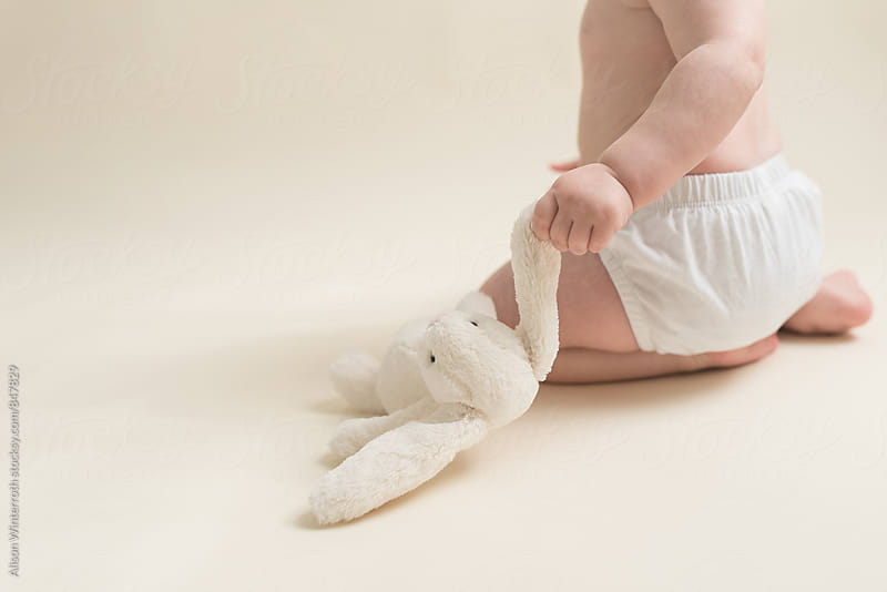 A Baby Holding Her Stuffed Bunny by Alison Winterroth for Stocksy United