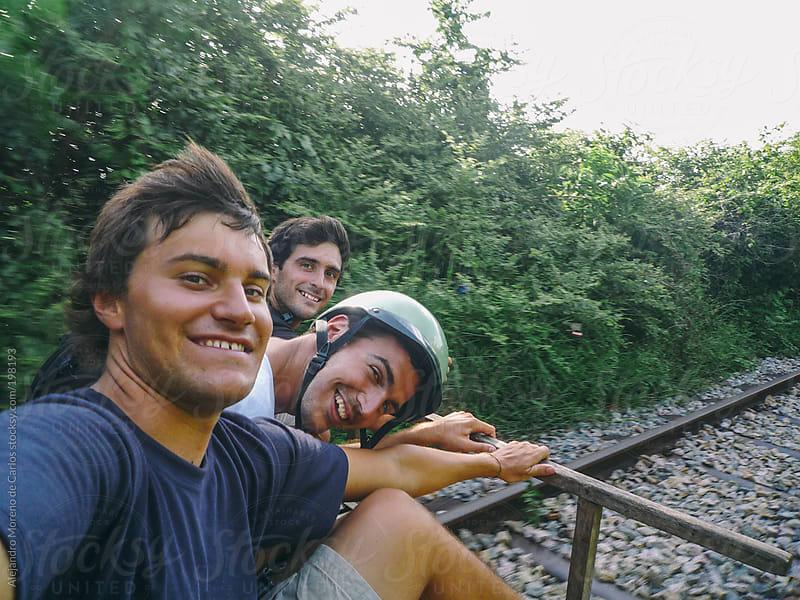 Three men friends on bamboo train in Cambodia by Alejandro Moreno de Carlos for Stocksy United