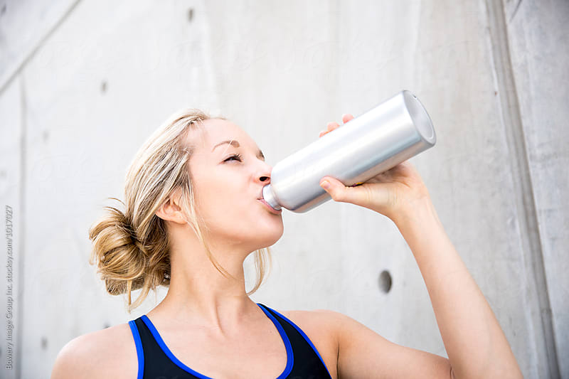 Woman drinking a water after her workout by Ann-Sophie Fjelloe-Jensen for Stocksy United