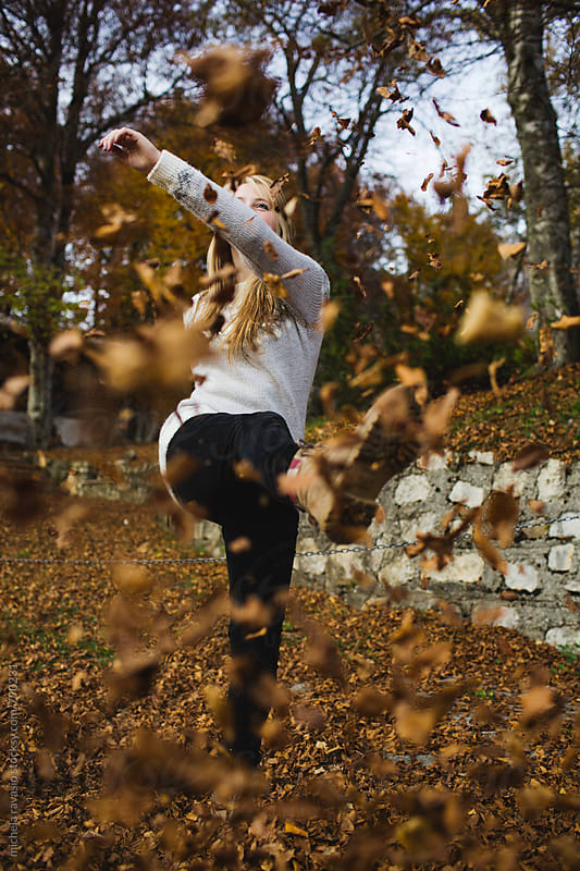 Girl kicking the dry leaves in woods by michela ravasio for Stocksy United