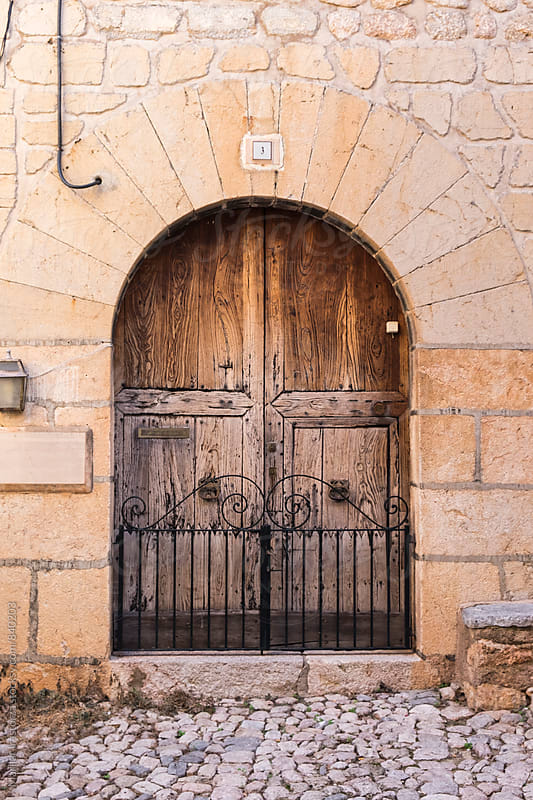Wooden door in a mediterranean village by Marilar Irastorza for Stocksy United
