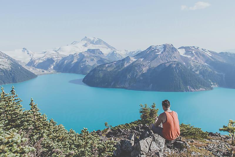 man alone above lake by Luke Gram for Stocksy United