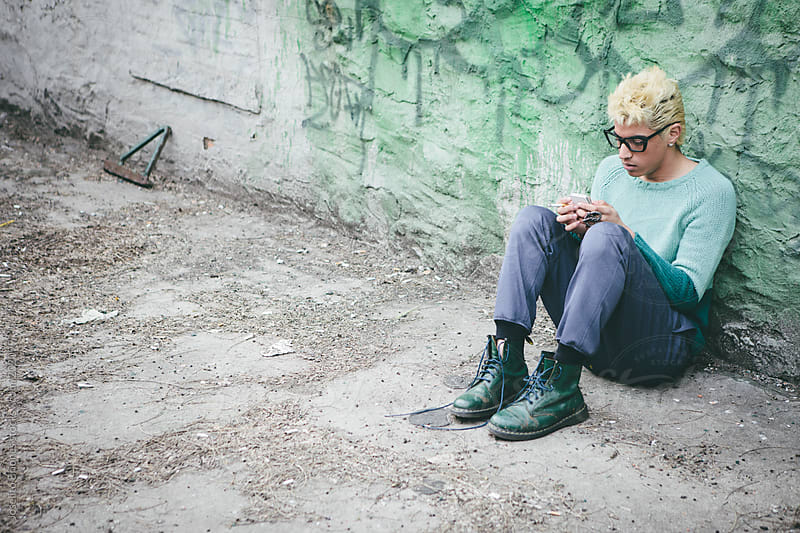 Stylish Young Man with Bleached Blond Hair Texting on Cellphone while Smoking a Cigarette by Joselito Briones for Stocksy United