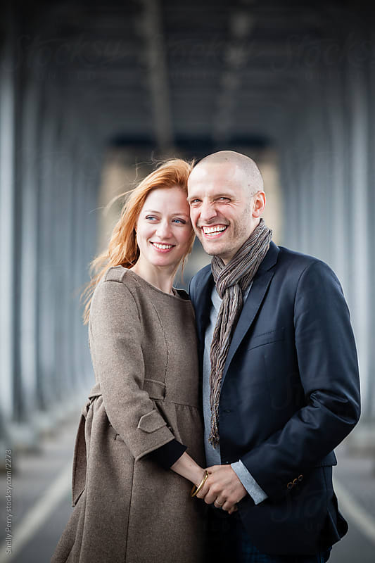 Smiling romantic couple in Paris, holding hands portrait by Shelly Perry for Stocksy United