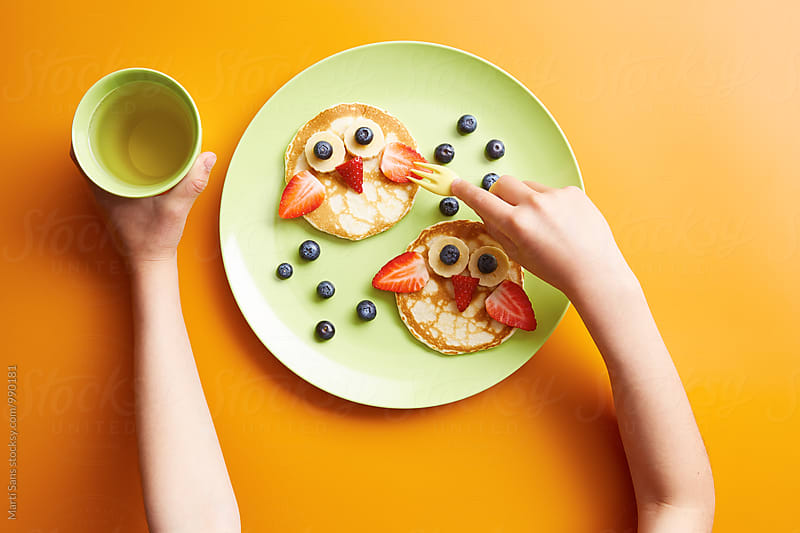 Kid eating owl pancakes with fork while holding glass by Martí Sans for Stocksy United