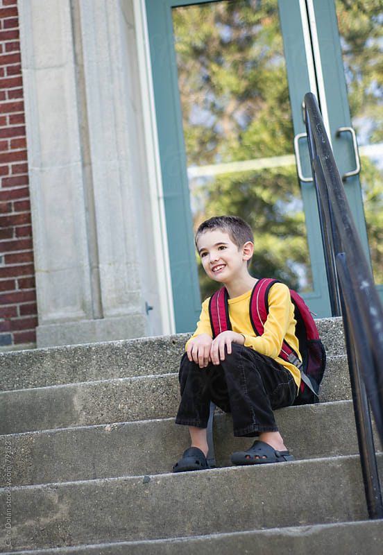 Smiling boy in backpack sits on the steps of a school by Cara Dolan for Stocksy United