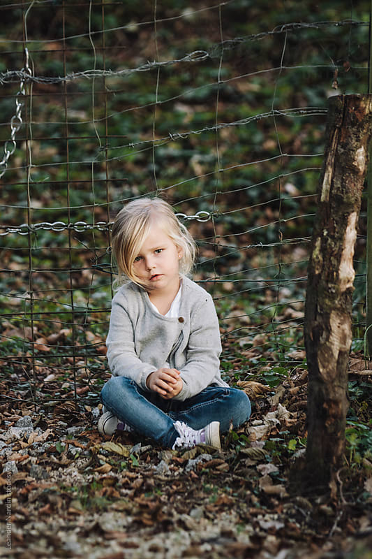 portrait of a sitting thoughtful looking cute little girl outdoors by Leander Nardin for Stocksy United