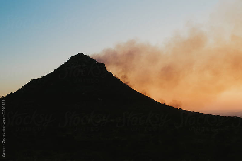 smoke from wildfire on mountain by Cameron Zegers for Stocksy United